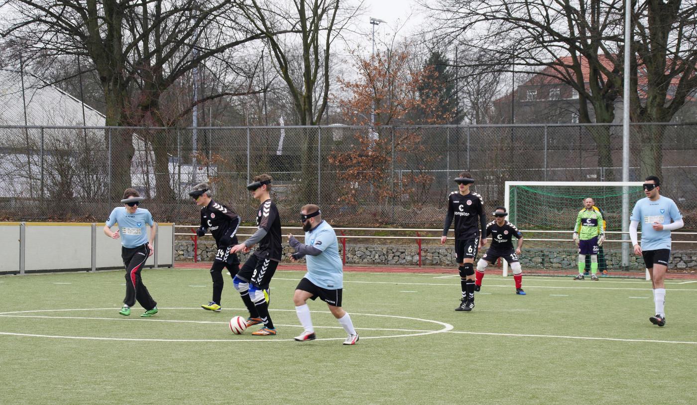 Eine Spielszene. Ein Spieler des FC St. Pauli führt den Ball in Höhe des Mittelkreises und wird von Ramon Pryssok attackiert. Wenige Meter weiter links bewegt sich Lars Stetten zum Ball um zusätzlich einzugreifen.