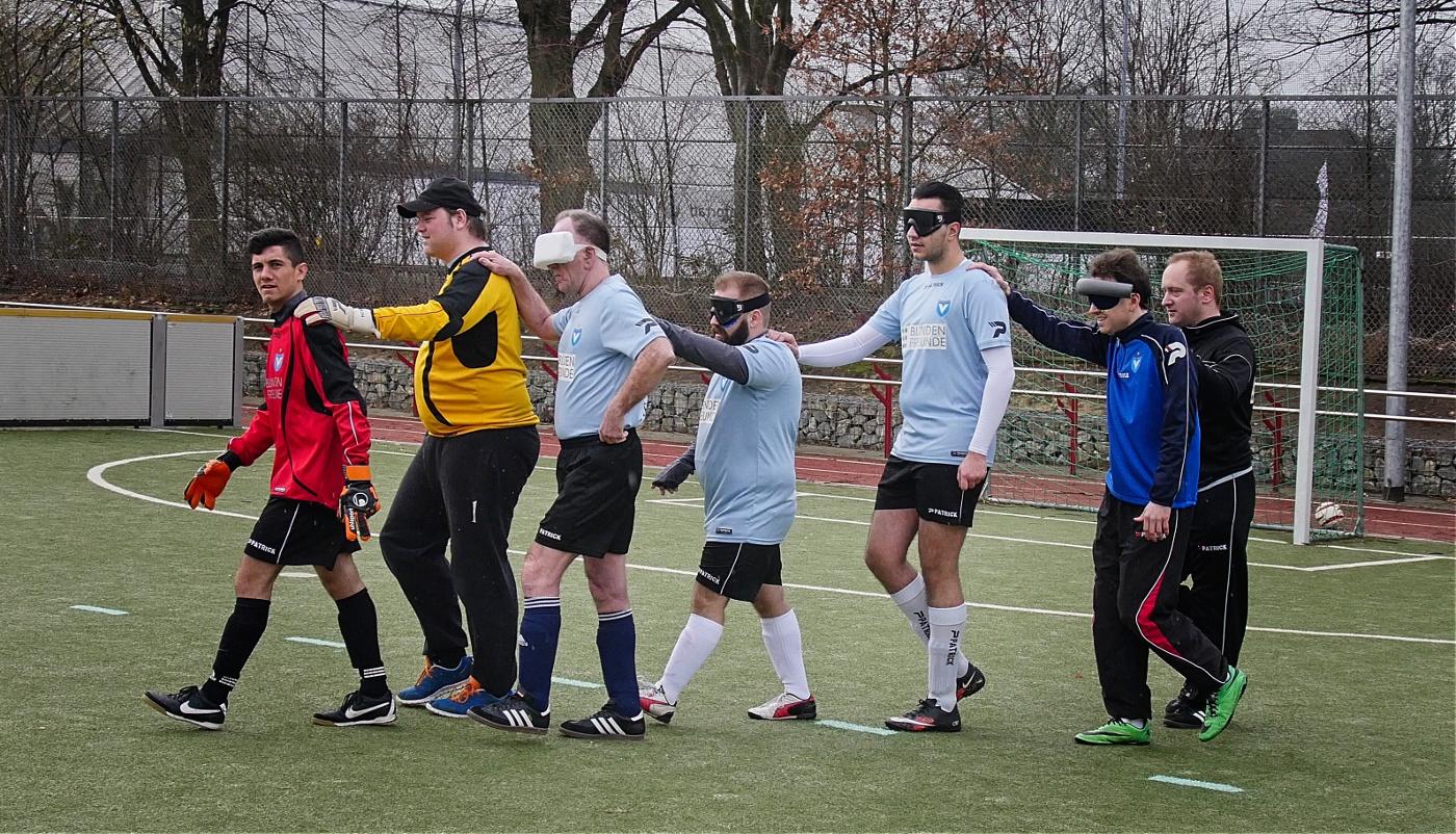 """Wie bei Punktspielen in der DBFL üblich laufen wir im """"Gänsemarsch"""" (hintereinander, zur Orientierung die Hand auf der Schulter des Vordermannes, der sehende Torwart voraus) von der eigenen Ecke zum Mittelpunkt, wo wir auf den Gegner treffen, der dasselbe gemacht hat. Dies dient der Vorstellung der Teams für das Publikum und wird vom Shake-Hands gefolgt, um sich gegenseitig rituell Fair Play zu versichern."""