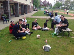 Eine Aufnahme, bei dem Spieler und Betreuer auf dem Rasen des Sportgeländes bzw. auf einer Bank sitzen.