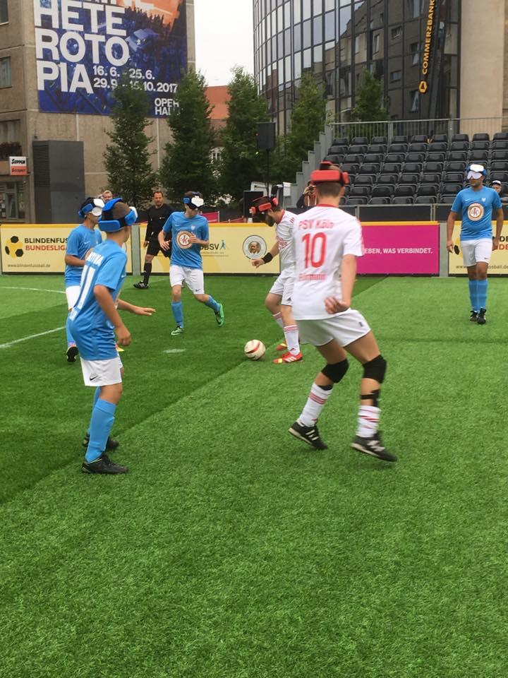 Spielszene. Stürmer von Köln/Köppern führt den Ball zentral etwa 9 Meter vom Tor der SG Berlin/München entfernt. Etwa 2 Meter vor ihm erwartet ihn Nasser Alwan. Links von Nasser hält sich Lars Stetten bereit einzugreifen. Leicht nach rechts vorne versetzt deckt Nico Rother einen weiteren Angreifer.