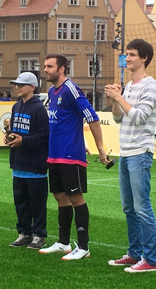 """Niko Rother steht auf dem Spielfeld (mittlerweile umgezogen) und hält die Trophäe für den """"besten Newcomer"""" in der Hand. Neben ihm steht der Chemnitzer Sebastian Themel mit der Trophäe für den """"besten Torhüter""""."""